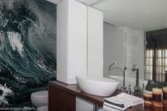 The wave mural and iroko vanity with custom made cabinet give a dramatic touch at this bright bathroom, designed by #eNJOY architects