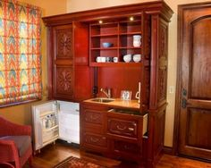 Master Bedroom Kitchenette install custom glass-front cabinetry to house luxurious bath