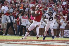 Oklahoma's CeeDee Lamb (9) catches a touchdown pass beside West Virginia's Elijah Battle (19) during a college football game between the Oklahoma Sooners (OU) and the West Virginia Mountaineers at Gaylord Family-Oklahoma Memorial Stadium in Norman, Okla., Saturday, Nov. 25, 2017. Photo by Bryan Terry, The Oklahoman