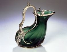A Victorian silver mounted cut green glass claret jug by John Figg, London 1840. After the antique, cut with flutes, the mounts formed as a branch handle issuing fruiting vines.