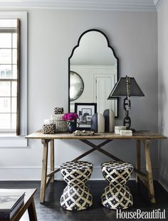 The corner of the bedroom features a mirror from Mecox, a console table by B.D. Jeffries and stools from Palecek.