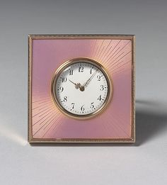 A square clock by Fabergé, gold, enameled translucent pink over a sunburst guillochage emanating from an opaque white enamel dial, the edge engraved with a dot-dash motif. Workmaster: Henrik Wigström, St. Petersburg, 1908-1917.