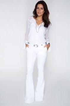 Bata branca de manga longa com bordados e calça branca flare. A proposta total white é chique e uma ótima opção para a virada do ano.