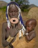 The Mursi women are famous for wearing plates in their lower lips. These lip discs are made of clay. Girls are pierced at the age of 15 or 16. Similar body ornaments are worn by both sexes of the Suyá people, a Brazilian tribe.