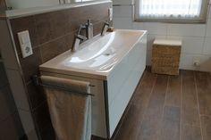 schönes Bad mt Holzoptikfliesen Waschtischunterschrank von Keuco