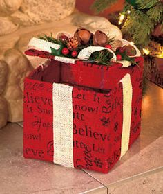 """Add a country note to your holiday decor with this rustic piece made of natural burlap. The Gift Box is a functional container (8"""" x 6"""" sq.) with a top that lifts open. Use it as a gift box or as storage for other holiday decorations. It's trimmed with 3 jingle bells, natural-looking evergreen sprigs and pine cones. Burlap and metal. Imported. Gift Box has a functional lid Details: Gift Box, 8"""" x 6"""" sq., burlap and metal"""