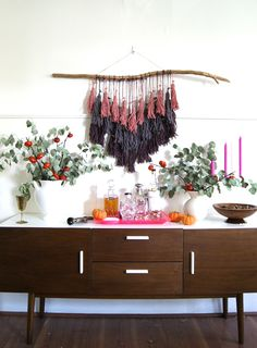 I created this DIY for my bohemian-inspired Friendsgiving party on Sunday.   It would make a great year-round wall hanging, could be done in more  festive colors for a more holiday look, or even done on a larger scale for  an impactful wedding detail.  Supplies      * yarn - I used three colors     * scissors     * branch or dowel - I painted mine gold     * twine, if you don't want to hang it from the string     * books of different sizes  Step 1 - Wrap one of the string colors around one…