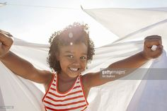 Stock Photo : Young girl smiling, holding white sheet