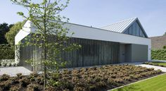 Voorgevel met translucente glazen wand met berkenboomstammen (de OTTENVANECK architecten & vormgevers)