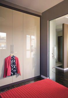 MIESZKANIE. Funkcję garderoby pełni pojemna szafa wnękowa z drzwiami ze szkła lacobel  w beżowym kolorze. Wystrój sypialni ożywiają czerwne elementy.