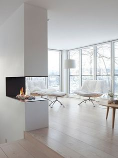 open fire place in neutral and white living room with a view