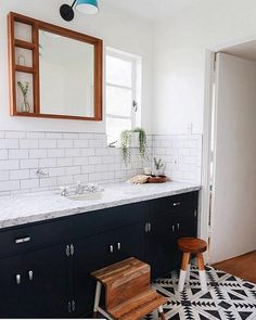 Rich wood accents warm up the graphic black and white floor tiles and coordinating cabinets in this modern bohemian bathroom.