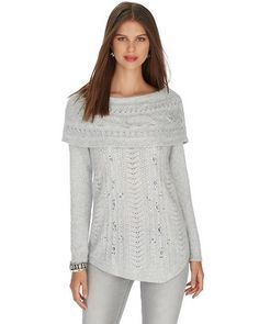 Cozy cable knit sweater gets a modern update with flattering asymmetrical hem, over the shoulder neckline and sparkling crystal embellishments. Stylist Note: Stock up your sweater collection— snuggable sweater with a bit of feminine flair is a must-have when paired with anything from your favorite jeans to a tapered pant.