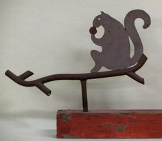 "Sold $400  Folk art sheet iron squirrel weathervane eating nut perched on round iron ""branch"". Appears to retain its original gray and brown paint. Excellent condition. Early 20th century. 21""L x 9""H."