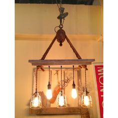 Edison bulb pendant under a whitewashed solid oak frame being suspended by rope from an old barn pulley.