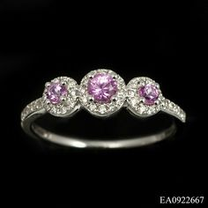 Delightful 3 stone pink sapphire and diamond ring in 18ct white gold. This beautiful design comprises of 3 x oval cut pink sapphires (.41ct total) each surrounded by a round cut diamond border (.19ct total). The centre stones are claw set on a low mount and narrow shank, a modern twist on a traditional design. £700
