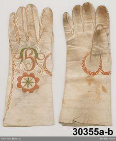 1 par handskar av vitt skinn.  På handens ovansida silkebroderier. Västbo.