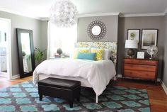 Taupe-gray walls with aqua and yellow accent pillows