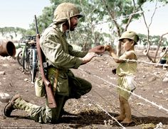 A marine passes a gift to boy through a barbed wire fence at an internment camp in Tinian in theNorthern Mariana Islands. The Pacific island hosted the Battle of Tinian in July and August 1944, when the 9,000-man Japanese garrison was wiped out