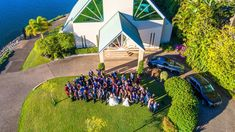 Aerial photo of the wedding couple and their guests outside the glass chapel at the Intercontinental Sanctuary Cove resort. Photo by Motion Art Wedding Films