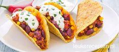 Makkelijk recept voor chili con carne geserveerd in taco schelpen met een schep zure room