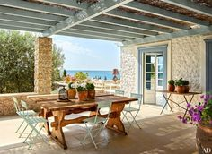 At a family's retreat on the Greek island of Spetses, park-style chairs surround a pair of hearty antique refectory tables on a terrace; decorator Isabel López-Quesada and architect Nikos Moustroufis designed the property, which includes a main dwelling and two smaller adjoining residences.