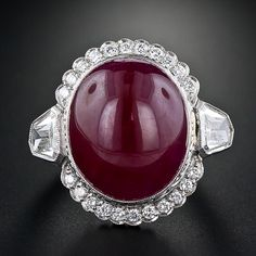 his deep, translucent, cherry-red oval cabochon ruby tops the scales at 26.66 carats! It is bezel-set and surrounded by a scalloped border of round brilliant-cut diamonds with a large calveshead shape diamond enlivening each shoulder. Milgrain and engraved details finish this bold, stunning and impressive platinum ruby and diamond ring.