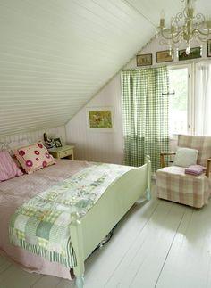 Pastellivärit sävyttävät makuuhuonetta. Karin ompeli tilkkupeitot jokaiselle lapselle. Vaaleanpunainen päiväpeite on Pentikistä. Nojatuoli on kirpputorilöytö. Karin päällysti sen Laura Ashleyn kankaalla.