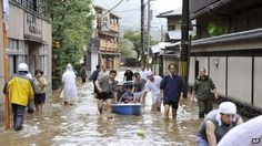 Hotel guests get a boat ride through a flooded street after the Katsura river was overflooded by torrential rains caused by a powerful typho...