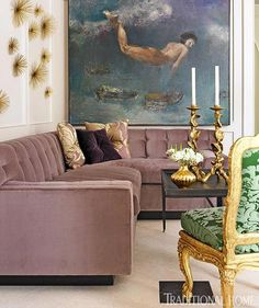 A large-scale painting and sea urchin-like wall art add personality to this sitting area, which is furnished with a purple sectional and gold details - Traditional Home® / Photo: Emily Followill / Designer: Melanie Turner