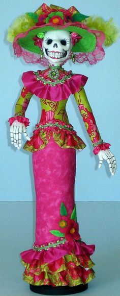 "AB510E  La Catrina Cloth Doll Pattern  Designed Arley Berryhill in the style of a traditional Calaveras, this high society lady is the iconic symbol for the Mexican holiday Dia de los Muertos (Day of the Dead). Measuring 18"" tall, La Catrina is a stump doll attached to a wood base. Pattern includes instructions for the hat and all accessories. White craft velour is recommended for head and hands."