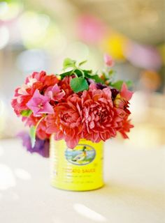 Red and fuchsia blooms in an old tin can
