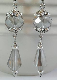 These unique earrings are made with light gray faceted glass crystal beads and pewter beads and bead caps. The antiqued pewter bead caps have a swirl motif. These earrings have a lot of movement and the faceted crystals catch and reflect light beautifully. The earwires on these