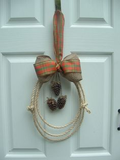 Sisal rope with burlap and fall colored bow, decorated with pine cones. Probably not big enough for a door, but an inside fall decoration! $5