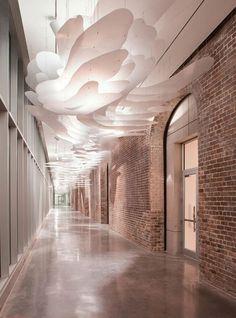 Trần được tạo từ các lớp vật liệu dược chiếu sáng tạo nên cảm giác bay bổng nhẹ nhàng tương phản với nền là mảng tường gạch trần nặng nề