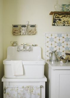 Charmed by this sweet little laundry, we shopped for an efficient washer and dryer slim enough to fit in the tiniest space, and a country-style Kohler utility sink for soaking adds farmhouse style. Cheery tile, colorful knobs, and floral fabric finish it off. A white palette with touches of blue in the hardware and backsplash is light and fresh—like clean laundry!