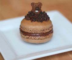 """Attach a mini chocolate chip to the face of a chocolate Teddy Graham with frosting, and add some white decorator candies for the teeth. Voila, you've got yourself a mini groundhog. The """"dirt"""" on top of the macaron is a mixture of chocolate frosting and crushed Oreos."""