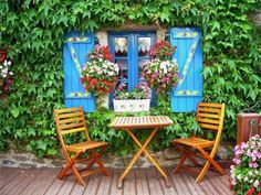 Bright Shutters and widow with embroidered curtains , flowering vine, hanging flower baskets. Planter. Cafe chairs and table. Stonework foundation. (posted on loveliegreenie/tumblr. January 24, 2012)