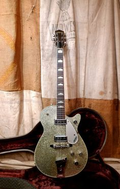 This Gretsch Silver Jet was made in Brooklyn in 1956. This guitar has seen lots of action and shows significant wear. The back and sides show significant finish checking including some flaking. There is an old pro headstock repair that is totally stable. The top is in very good shape and has ...