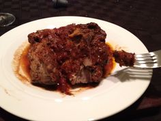 Brasato di Maiale Nero from Mario Batali's Molto Italiano cookbook. Pork shoulder is braised in an olive oil/pancetta/garlic/parsley base, then slow-cooked in a crushed tomato/Chianti sauce. By the time it's done, you need not use a knife - it will fall apart just using a fork. For a nice aromatic touch, stuff the pork shoulder with fresh sage leaves before braising.