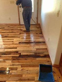 This step by step tutorial shares how to create inexpensive wood flooring DIY building project from reclaimed wood from free wood pallets.