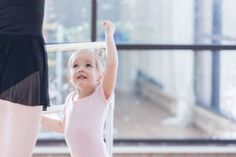 Adorable little ballerina listens to instructor at ballet barre