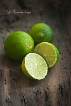 Limes {Food Photography} Close-up on several limes, on a dark wooden plank.  Shot done using a macro lens and natural window light.