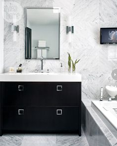 Hotel-style glam With its clean and sophisticated style, and glamorous touches of silver in the hardware, mirror and sconces, this bathroom makes you feel as though you've checked into a five-star hotel.