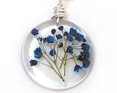 This listing is for a lovely pendant of several gorgeous red babys breath flowers encased in jewelers grade resin. The pendant is a donut shape. I have wire wrapped a silver tone wire through a hole at the top that acts as a bail. This would be a wonderful gift for Mothers Day or any day! It is a fun shape and substantial size for a wonderful statement pendant! Please note that the back of the pendant is flat and not rounded like the front of the pendant.   The pendant measures about 1 1/2…