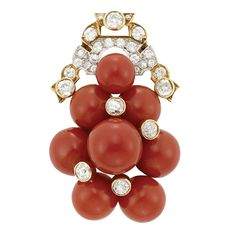 Art Deco Gold, Oxblood Coral Bead and Diamond Clip-Brooch, circa 1935.  Centering a cluster of 7 coral beads approximately 12.4 to 8.8 mm., accented by 4 collet-set old-mine cut diamonds, topped by an openwork plaque set with 23 old-mine cut and round diamonds, totaling approximately 2.35 cts.
