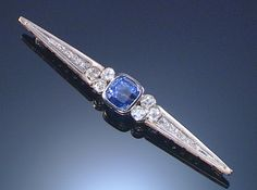 SAPPHIRE AND DIAMOND BROOCH The central cushion-shaped sapphire between circular-cut diamonds to a tapering bar set with single-cut diamonds, length approximately 78mm.