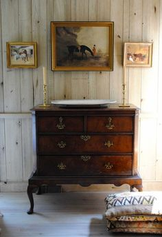 Rustic walls and floors, pretty antique dresser, candlesticks and artwork