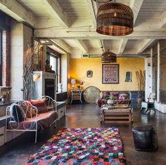 salon de style hippie chic avec un tapis multicolore, banc en fer forgé blanchi et abat-jour de style rustique
