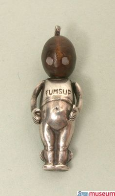 """'Fums up' lucky charm. 'The 'Fums up' lucky charm was a popular trinket given to servicemen, usually by their sweethearts. The head is made from wood so its owner would """"touch wood"""" for good luck."""